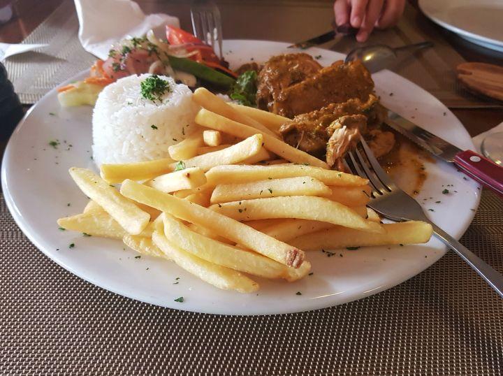 Foto de uma das refeições deliciosas de Aruba: essa se chama galinha stoba, tem arroz, batata frita e uma galinha temperada de forma diferente que não sei descrever, só provando pra saber